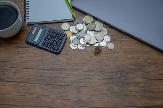 Silver coins, computer calculators and white coffee cups placed on a brown desk.Green pencil and white book on the table.Do not focus on objects.