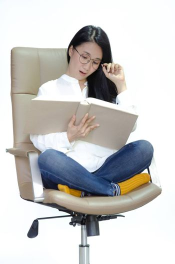 A woman wearing a white shirt, wearing glasses on a chair, yellow socks, holding a pencil and a book on a lap. She has doubts.