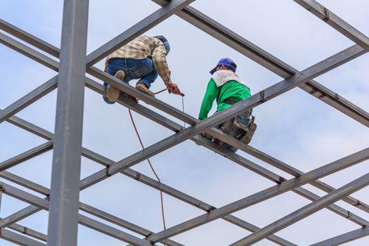 Welder welding fabricated construction in building, Welding process by Stick Welding, No safety Belt, No Mask, No Glove