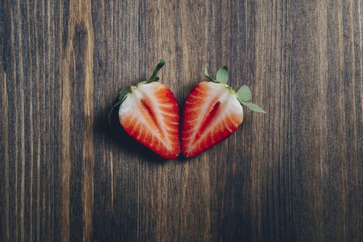 couple strawberry slice cut in half on wooden background in rustic style, healthy sweet food, vitamins and fruity concept. Top view, copy space for text