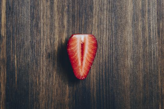 half strawberry on a wooden table in rustic style. Top view, copy space for text