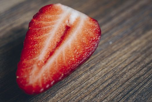 half strawberry on a wooden background in rustic style, copy space for text