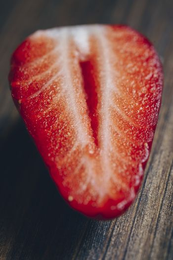 vertical photo of a half strawberry on a wooden table in rustic style