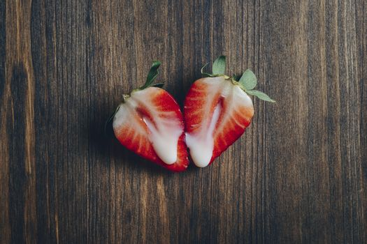 metaphor of sex with strawberries and milk on a wooden background, top view, copy space for text