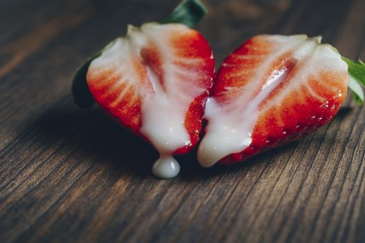 metaphor of sex with strawberries and milk in a wooden background, top view, copy space for text
