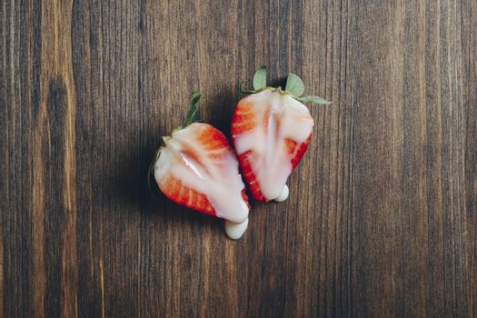 metaphor of sex with strawberries and milk on wooden background, top view, copy space for text