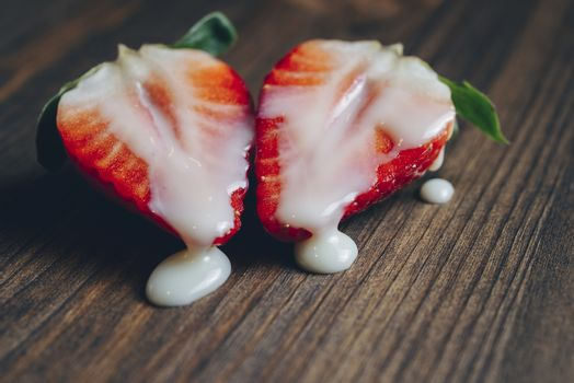 metaphor of sex with strawberries and milk in a wooden table, top view, copy space for text
