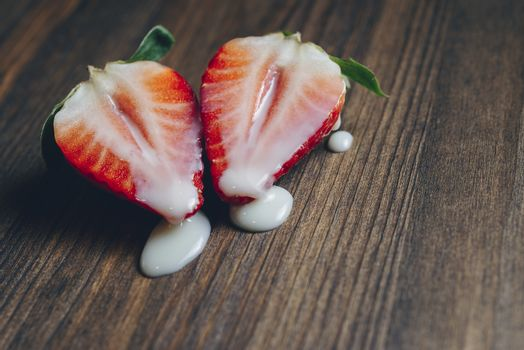 metaphor of sex with strawberries and milk on a purple wooden background, top view, copy space for text