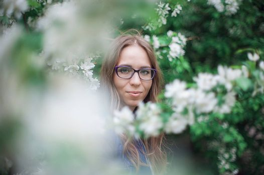 Beautiful woman portrait in the blooming garden of apple