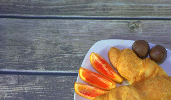 Fragment of a plate on the table with croissants, chocolates and orange slices.