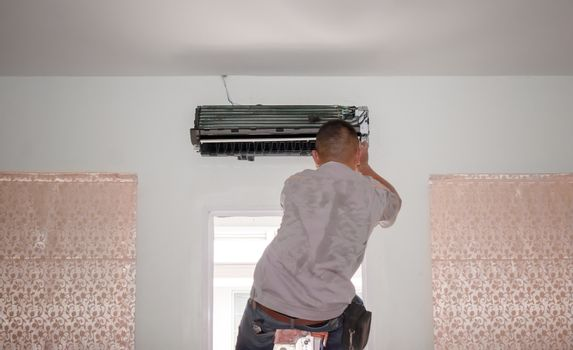 Air Conditioning Repair Man Works on an AC Unit in a Residence