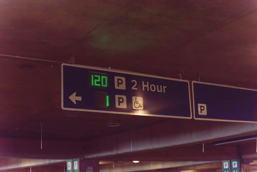 Overhead neon sign at indoor American airport parking lot displays number of available parking spaces. Available empty spots display counter information. 2 hour parking limitation
