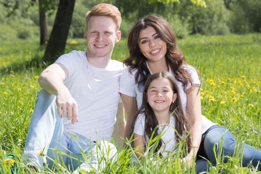 Portrait of happy smiling family of parents and girl sitting on grass with dandelion flowers at sunny summer day
