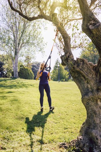 vertical photo of a beautiful young woman training outdoors under a tree, fitness girl workout with suspension equipment at the morning in a sunny park