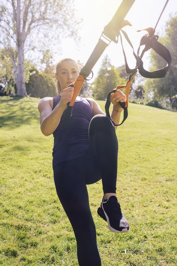 vertical photo of a young beautiful woman doing exercises outdoors under a tree, fitness girl workout with suspension equipment at the morning in a sunny park