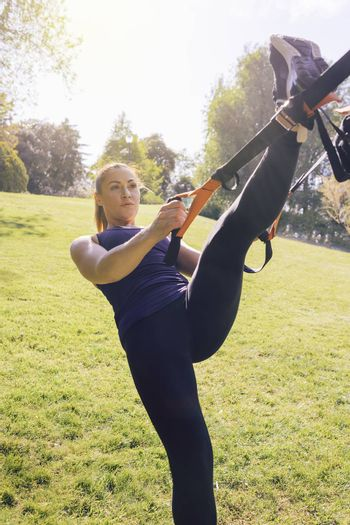 vertical photo of a beautiful young woman doing exercises outdoors under a tree, fitness girl workout with suspension straps at the morning in a sunny park