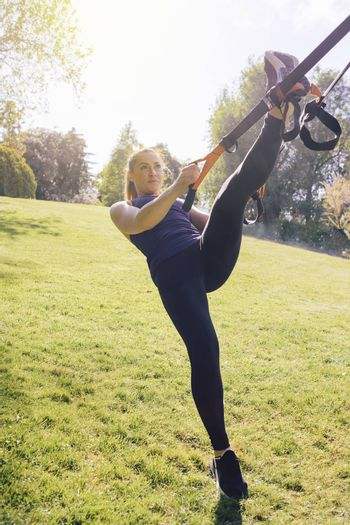 vertical photo of a beautiful young woman training outdoors under a tree, fitness girl workout with suspension straps at the morning in a sunny park