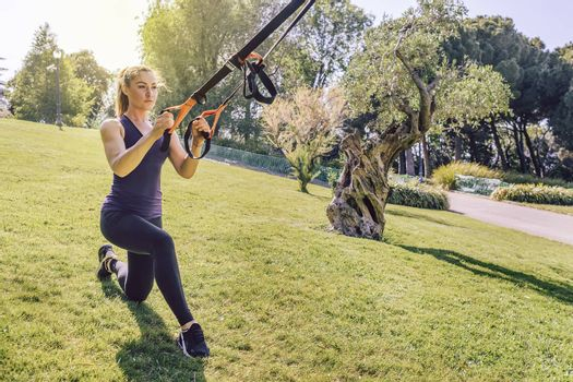 attractive young woman doing fitness and training with suspension straps, she is outdoors during functional workout