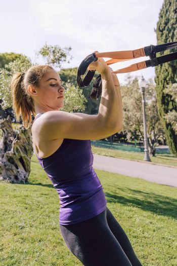 vertical photo of a strong young woman training biceps with suspension fitness straps, she is outdoors during functional workout