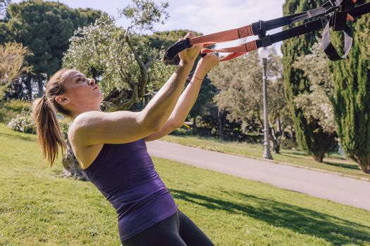 athletic young woman doing bicep curls with fitness suspension straps, during functional workout in a outdoor park
