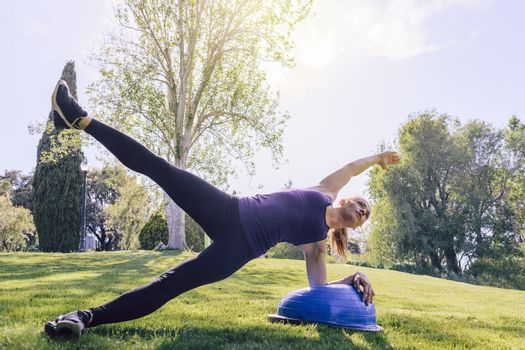 healthy young woman planking on the grass on a sunny day, she is outdoors in a park at the morning