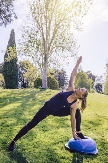 vertical photo of a healthy young woman doing stretching yoga workout on the grass on a sunny day, she is outdoors in a park at the morning