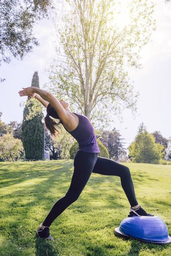 vertical photo of a healthy young female doing stretching yoga workout on the grass on a sunny day, she is outdoors in a park at the morning