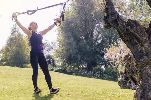 athletic young woman training with fitness suspension straps, during functional workout in a sunny outdoor park in the morning