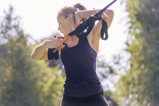athletic woman training with fitness straps, during functional workout in a sunny outdoor park in the morning