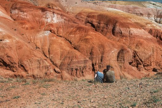 Relaxing man and woman in Valley of Mars landscapes in the Altai Mountains, Kyzyl Chin, Siberia, Russia
