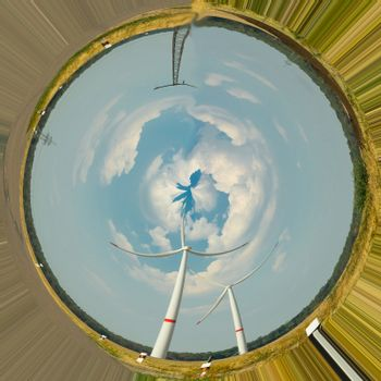 Wind turbines for renewable energies. Photo effect with distortion filter in front of blue sky