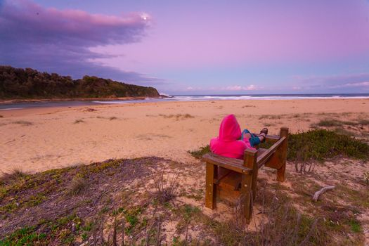 Woman relaxes on bench overlooking beach in the afternoon dusk