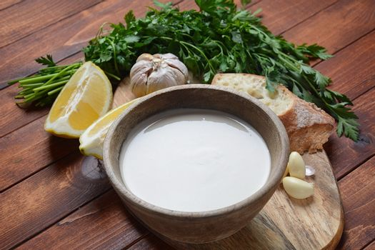 Tahini sauce made from sesame seeds in bowl with parsley on wooden background
