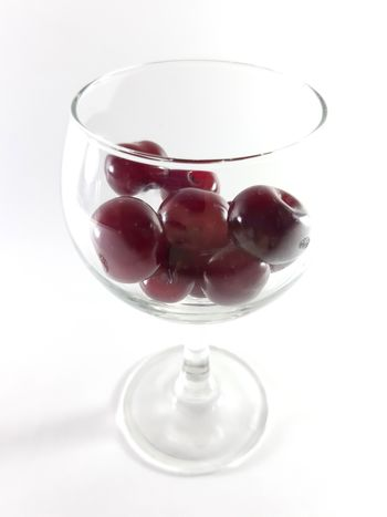 Cherry fruit in transparent wineglass. Cherry for a snack. Photo isolated.