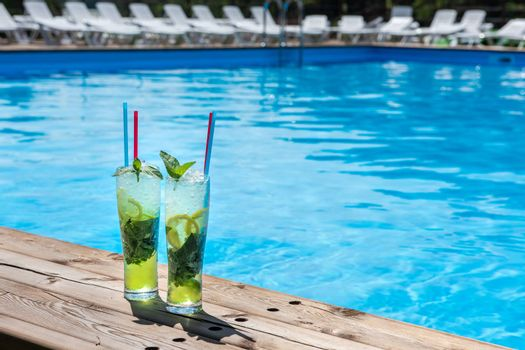 Two Mojito cocktail with lime and mint in highball glass on the swiming pool background. Concept of summer relaxing