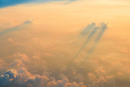 Beautiful aerial view of clouds at sunset, some clouds projecting dramatic shadows. View from airplane.