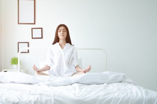Asian girls sitting on yoga poses in bed in a warm morning.Warm tone.Do not focus on objects.
