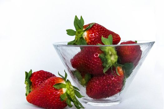 some strawberries in a glass cup and two of them outside