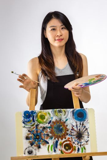 Artist standing behind painting holding palette and brush