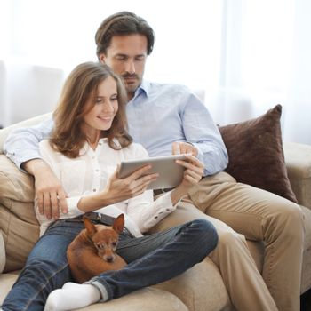 Happy couple using digital tablet at home sitting together with dog on sofa