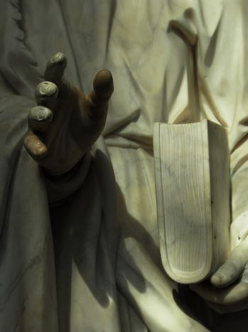 details of ancient statue, a hand and a book in low light