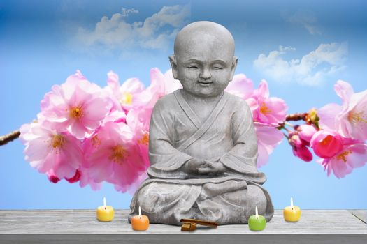 Buddha stone statue child background cherry blossom lighted candles and incense
