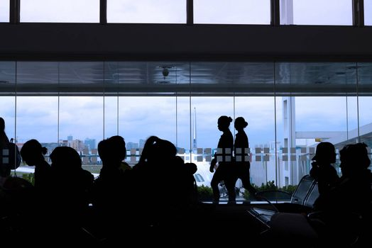 silhouette of crew and passengers at an airport lounge