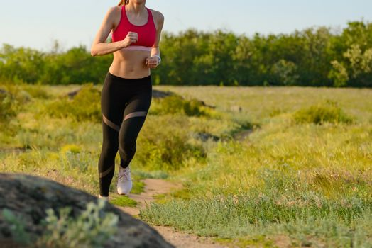 Woman Running on the Mountain Trail in the Hot Summer Evening. Sport and Active Lifestyle.