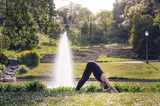 young sporty woman doing meditation yoga exercises and relaxing outdoors in the park, modern healthy lifestyle and sport concept