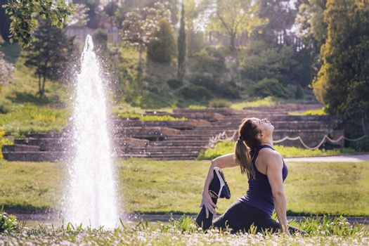 young sports girl doing meditation yoga exercises and relaxing outdoors in the park, modern healthy lifestyle and sport concept