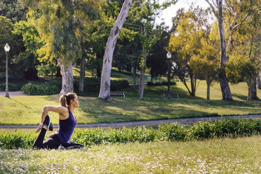young sports woman doing meditation yoga flexibility exercises and relaxing outdoors in the park, modern healthy lifestyle and sport concept