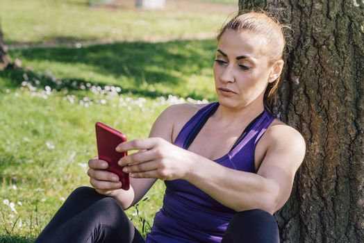 fitness woman taking a workout rest sitting next to a tree for texting on her phone, healthy modern lifestyle and sport concept