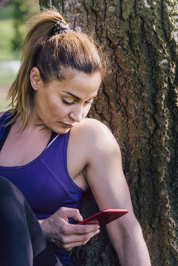 fitness woman taking a workout rest sitting next to a tree for take a look to her phone, healthy modern lifestyle and sport concept