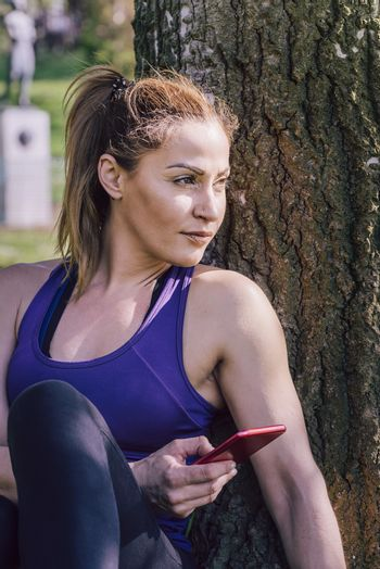 sports woman resting after exercise to take a look to her phone while sitting next to a tree, healthy modern lifestyle and sport concept